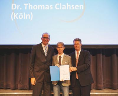Dr. Stephan Schulz von Heidelberg Engineering (links) und Prof. Dr. Claus Cursiefen von der DOG (rechts) übergeben Dr. Thomas Clahsen den gestifteten Patent-Preis.