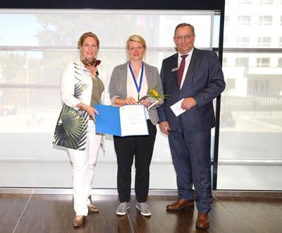 Prof. Dr. Nicole Eter von der DOG (links) und Erich Bangert (Heidelberg Engineering) übergeben Frau Dr. José Hurst (Vertretung von Dr. Schnichels) den gestifteten Patent-Preis.
